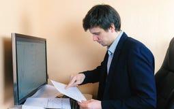 L'uomo lavora ad un computer Confronta i grafici sullo schermo e su carta Fotografia Stock