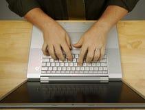 L'uomo lavora al suo computer portatile Fotografia Stock Libera da Diritti