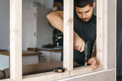 L'uomo lavora come cacciavite, riparante una struttura di legno per la finestra alla divisione del pannello di carta e gesso del  fotografie stock libere da diritti