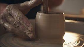 L'uomo lavora con una ruota del ` s del vasaio, soltanto mani Elaborazione dell'argilla stock footage