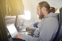L'uomo lavora dietro il computer portatile in salone l'aereo Immagini Stock Libere da Diritti