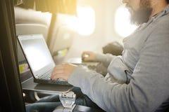 L'uomo lavora dietro il computer portatile in salone l'aereo Fotografia Stock Libera da Diritti