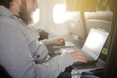 L'uomo lavora dietro il computer portatile in salone l'aereo immagine stock
