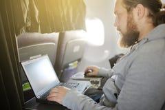 L'uomo lavora dietro il computer portatile in salone l'aereo immagini stock