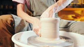 L'uomo lavora le sue mani con argilla Processo di creare prodotto da argilla sul tornio da vasaio Vista laterale dell'artigiano c video d archivio