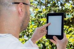 L'uomo legge un libro elettronico in un giardino Fotografia Stock Libera da Diritti
