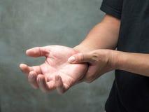 L'uomo lo tiene lesione di mano del polso, ritenente il dolore Sanit? e conept medico immagini stock