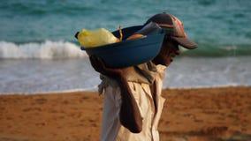 L'uomo locale abbronzato porta il bacino blu con frutta sulla spalla video d archivio