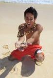 L'uomo locale sostiene un granchio della sabbia Fotografia Stock