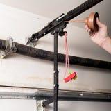 L'uomo lubrifica il rilascio rapido di un apri della porta del garage per tenerlo funzionare senza difficoltà fotografie stock