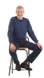 L'uomo maggiore felice si siede con le mani sulle ginocchia. Fotografia Stock Libera da Diritti