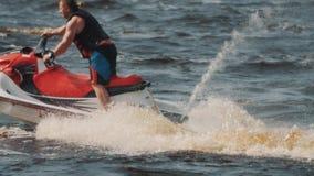 L'uomo in maglia di vita che mostra l'estremo gira e torce su un jet ski sulla velocità di altezza stock footage