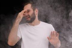 L'uomo in maglietta bianca su fondo nero odia il fumo della sigaretta fotografia stock