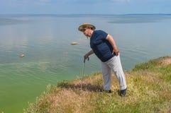 L'uomo in maglietta e nella luce blu ansima la condizione sulla riva del fiume brusca elevata del fiume di Dnipro fotografia stock