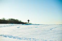 L'uomo in maglione caldo con una barba sta camminando sulla via nell'inverno in un giorno soleggiato caldo al fiume fotografia stock libera da diritti