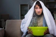 L'uomo malato che fa inalazione alla notte nella casa immagini stock