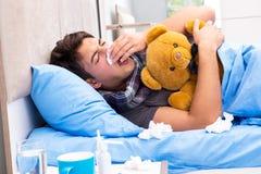 L'uomo malato con influenza che si trova nel letto fotografie stock