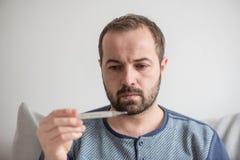 L'uomo malato controlla la temperatura corporea con un termometro a mercurio Tema delle malattie virali, influenza, freddo immagine stock libera da diritti