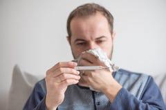 L'uomo malato controlla la temperatura corporea con un termometro a mercurio Tema delle malattie virali, influenza, freddo fotografia stock libera da diritti