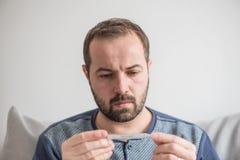 L'uomo malato controlla la temperatura corporea con un termometro a mercurio Tema delle malattie virali, influenza, freddo Effett immagini stock