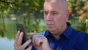 L'uomo manda un sms alle informazioni di affari facendo uso di un cellulare in parco archivi video