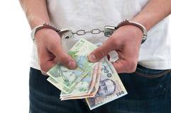 L'uomo in manette sta tenendo i soldi Immagini Stock