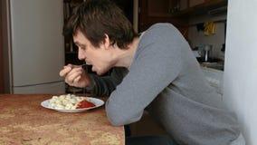 L'uomo mangia gli gnocchi con una forcella, mettente li nella salsa al pomodoro nella cucina video d archivio