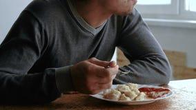 L'uomo mangia gli gnocchi con una forcella, mettente li nella salsa al pomodoro nella cucina archivi video
