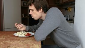 L'uomo mangia gli gnocchi con una forcella, mettente li nella salsa al pomodoro nella cucina stock footage