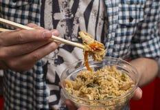 L'uomo mangia il riso fritto con i bastoncini per i sushi Fotografie Stock