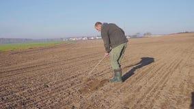 L'uomo manualy coltiva la terra con un giorno soleggiato della zappa archivi video