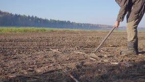 L'uomo manualy coltiva la terra con una fine della zappa su stock footage