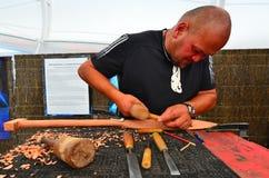L'uomo maori scolpisce una scultura di Maori Wood Fotografia Stock
