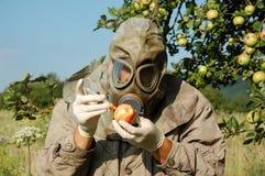 L'uomo in maschera antigas squirts la mela fotografia stock libera da diritti