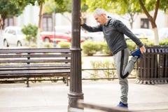 L'uomo maturo che fa una certa gamba allunga nella città Immagini Stock Libere da Diritti