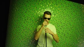 L'uomo maturo con gli occhiali da sole e la maglietta bianca balla e canta la tenuta del microfono stock footage