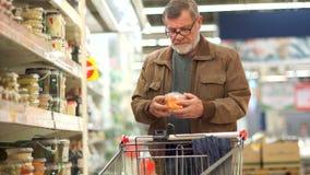 L'uomo maturo con una barba mette un'insalata della carota in un carrello in un supermercato Alimento sano, pensionato solo, fest video d archivio