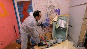 L'uomo maturo distrugge un vecchio frigorifero da una mazza nelle rovine archivi video