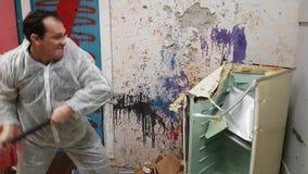 L'uomo maturo distrugge un vecchio frigorifero da una mazza nelle rovine video d archivio