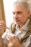 L'uomo maturo maggiore mangia lo spuntino del yogurt Fotografia Stock Libera da Diritti