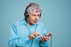L'uomo maturo prova ad imparare come la nuova applicazione di uso sullo Smart Phone, ascolta audio piste in cuffie, isolato sopra fotografie stock