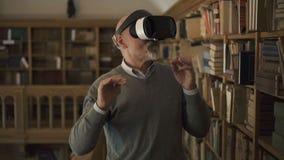 L'uomo maturo sta provando i vetri di realtà virtuale che stanno nella biblioteca d'annata archivi video