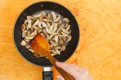 L'uomo mescola i funghi prataioli in pentola Fotografie Stock Libere da Diritti