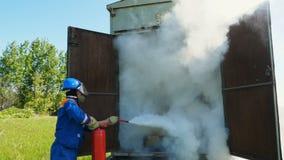 L'uomo mette fuori il fuoco con un estintore archivi video