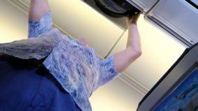 L'uomo mette il bagaglio a mano sullo scaffale superiore in un aeroplano del passeggero Vista dal basso concetto di corsa video d archivio