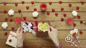 L'uomo mette il biglietto di S. Valentino di carta nella scatola attuale, vista superiore stock footage