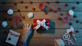 L'uomo mette il biglietto di S. Valentino sulla scatola attuale per la sua amica, vista superiore video d archivio