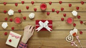 L'uomo mette il biglietto di S. Valentino sulla scatola attuale per la sua moglie, vista superiore video d archivio