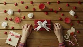 L'uomo mette il biglietto di S. Valentino sulla scatola attuale per il suo caro, vista superiore archivi video