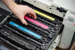 L'uomo mette il toner nella stampante fotografia stock libera da diritti